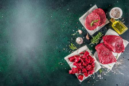 Various raw beef meat with spices and herbs, dark concrete background copy space Stockfoto
