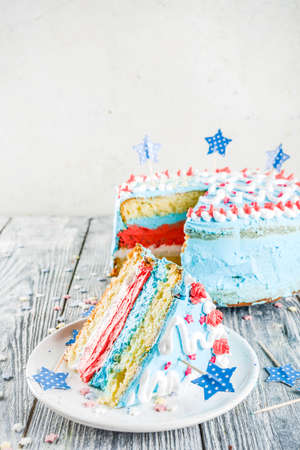 Homemade American United States  Independence day cake, for 4 July party, with sugar stars, striped cream decoration, wooden background copy space