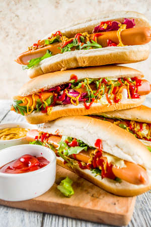 Homemade hot dogs with fresh greens, sausages and sauces, white wooden background copy space top view Standard-Bild - 121234304