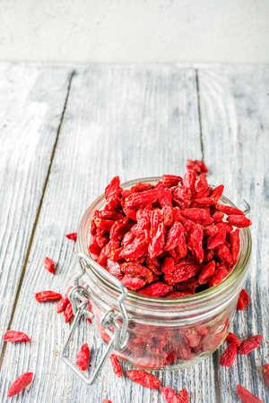 Dried goji berries in little jar, wooden background copy space