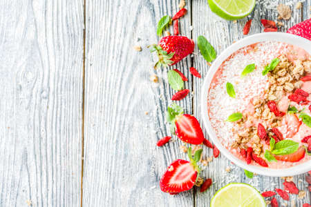 Healthy breakfast smoothie bowl with goji and strawberry berries, granola, yogurt, coconut, lime, wooden background copy space