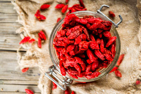 Dried goji berries in little jar, wooden background copy space Stock Photo