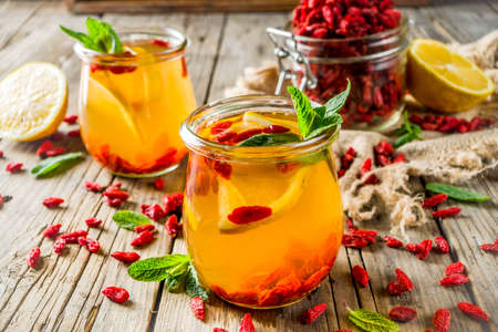 Homemade goji hot tea with mint and lemon slices, wooden rustic background copy space