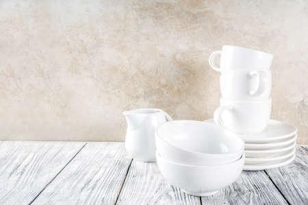 Asortyment stosu czyste puste nowe białe naczynia kuchenne, talerze, miski, kubki, kubki. Na białym betonowym tle