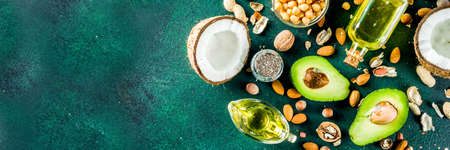 Healthy vegan fat food sources, omega3, omega6 ingredients - almond, pecan, hazelnuts, walnuts, olive oil, chia seeds, avocado, coconut, dark green background copy space banner