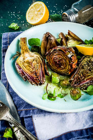 Cooked baked artichoke, alla romana, grilled artichoke flowers with olive oil, lemon, garlic, mint  and spices. Copy space