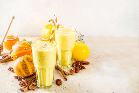 Healthy breakfast, snack. Spicy pumpkin smoothie with pumpkins, pecan nuts, honey, oatmeal, cinnamon, anise. Light concrete background copy space Imagens - 121465791
