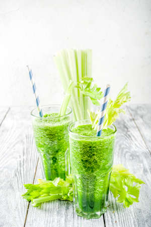 Healthy vegan food and drink. Diet green cucumber and celery smoothie cocktail, on a wooden background, Foto de archivo
