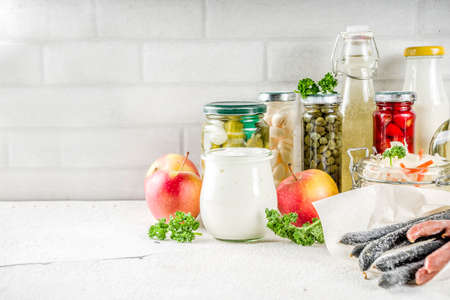 Assortment of various fermented food - apple cider vinegar, fermented meat and vegetables,  sauerkraut, pickled peppers, tomatoes, garlic, capers, white background copy space Stockfoto