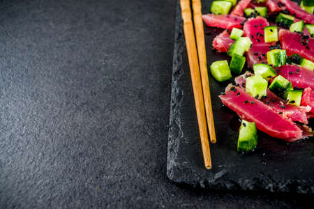 Tuna sashimi poke with raw fresh fish, cucumber, black sesame seeds and soy sauce, black stone background copy space