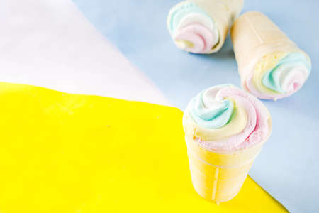 Multicolored pastel unicorn rainbow ice cream. Three colorful ice cream waffle cones on bright background copy space