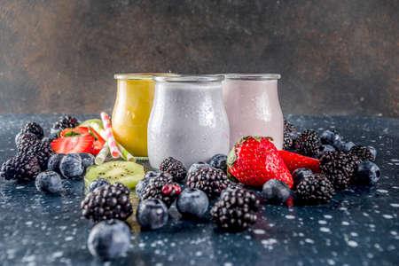 Summer fruits and berries smoothie drink. Vitamin diet snack beverage, with blueberries, strawberries, blackberries, kiwi. Dark blue concrete background copy space 版權商用圖片