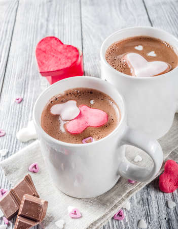 Valentines day treat ideas, two cups hot chocolate drink with marshmallow hearts red pink white color with chocolate pieces, sugar sprinkles, old wooden background copy space top view Фото со стока