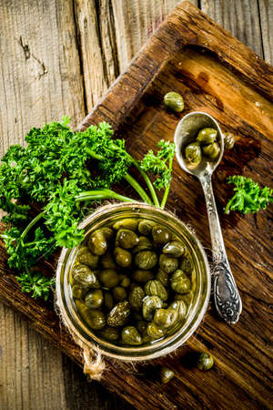 Pickled capers in little jar, with herbs on rustic wooden background copy space