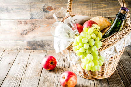 Picnic basket with food and drinks (fresh fruits, bread and wine bottle, glasses), copy space Reklamní fotografie