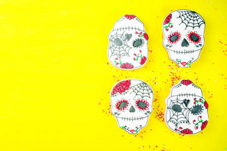 Dia de Los Muertos, Mexican Day of the Dead or Halloween greeting card background with traditional colorful skull shaped cookies with sugar topping candies top view copy space