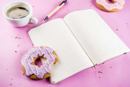 Rest and relaxation concept, coffee cup and biscuits donut with sugar coating, with a notepad for notes or wishes on a bright trendy background, top view space for text 版權商用圖片