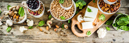 Healthy plant vegan food, veggie protein sources: Tofu, vegan milk, beans, lentils, nuts, soy milk, spinach and seeds. Old wooden background copy space banner