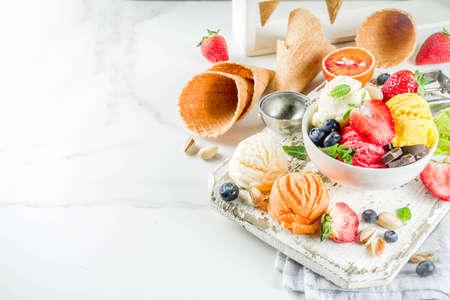 Colorido helado de frutas y bayas, nueces, chocolate y vainilla, con conos de helado de gofres, con frutas frescas y bayas, espacio de copia de vista superior fondo de mármol blanco Foto de archivo