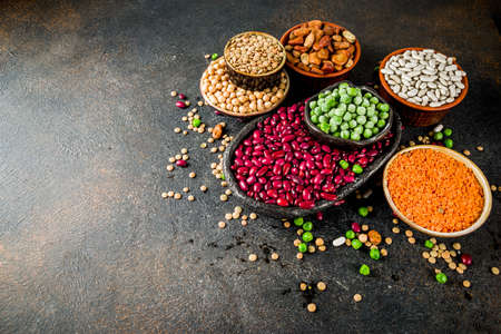 Various assortment of legumes - beans, soy beans, chickpeas, lentils, green peas. Healthy eating concept. Vegetable proteins. Dark concrete background copy space top view