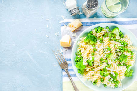 Pasta with green vegetables and parmesan cheese. Vegan fusilli pasta salad with broccoli and green peas, on light blue slate, stone or concrete background, top view copy space