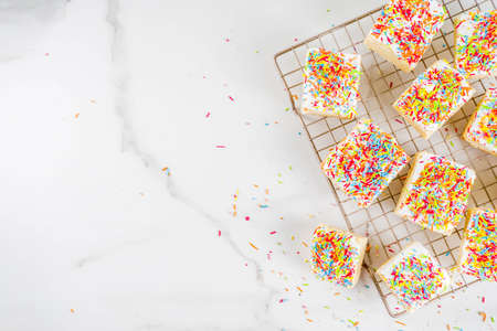 Frosted Sugar Cookie Bars, with sugar topping and colorful sugar crumbles, white marble background copy space 写真素材