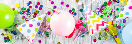 Birthday party decoration background with balloons, gift boxes, steamers and confetti, wooden white table copy space above banner