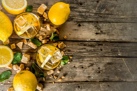 Lemonade or iced summer tea, with fresh lemon slices, sugar and mint leaf, rustic wooden table, copy space 스톡 콘텐츠