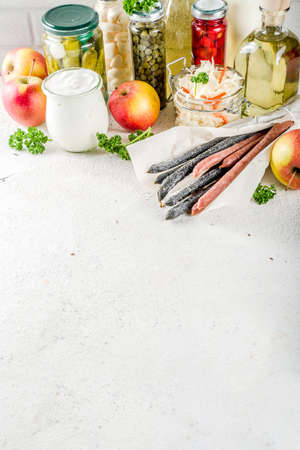 Assortment of various fermented food - apple cider vinegar, fermented meat and vegetables,  sauerkraut, pickled peppers, tomatoes, garlic, capers, white background copy space Reklamní fotografie