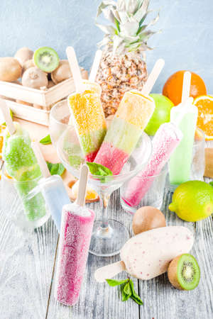 Colorful fruit ice cream . Juicy gelato lollypops on sticks, with different fresh tropic fruits, wooden background copy space