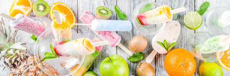 Colorful fruit ice cream  . Juicy gelato lollypops on sticks, with different fresh tropic fruits, wooden background copy space Stockfoto