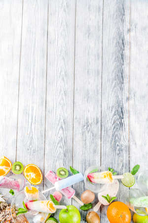 Colorful fruit ice cream  . Juicy gelato lollypops on sticks, with different fresh tropic fruits, wooden background copy space 版權商用圖片