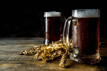 Two Homemade craft beer mugs, dark wooden background copy space
