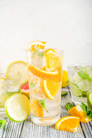 Summer refreshment drinks. Four types of citrus lemonade or mojito cocktail - orange, lime, lemon, pink grapefruit. Infused citrus water. On a wooden white background, Stock Photo