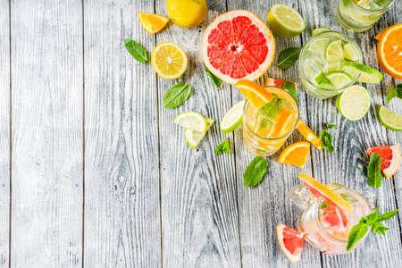 Summer refreshment drinks. Four types of citrus lemonade or mojito cocktail - orange, lime, lemon, pink grapefruit. Infused citrus water. Stock Photo