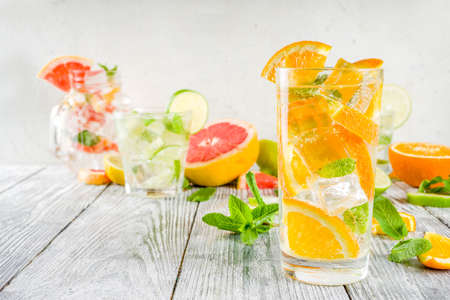 Summer refreshment drinks. Four types of citrus lemonade or mojito cocktail - orange, lime, lemon, pink grapefruit. Infused citrus water. On a wooden white background Stock Photo