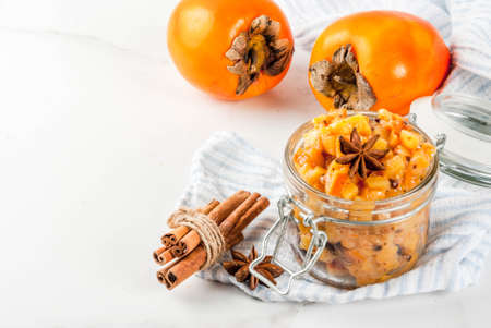 Traditional indian food recipes, Persimmon fruit Chutney with cinnamon and anise stars, white marble background copy space