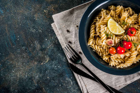 Classic italian pasta fusilli with pesto sauce, tomatoes, lime and fresh herbs in dark bowl, dark blue background copy space top view