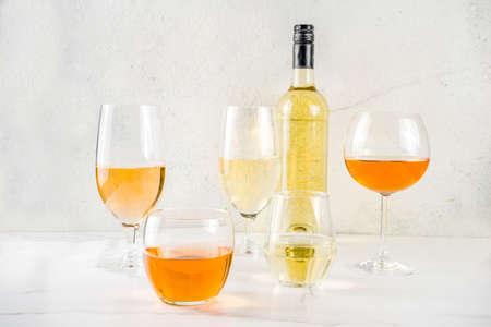 Trendy orange wine, with white wine in different glasses, white concrete background copy space Imagens
