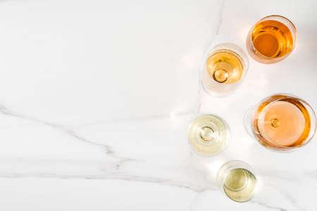 Trendy orange wine, with white wine in different glasses, white concrete background copy space Stockfoto
