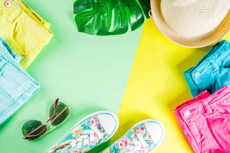 Summer sale shopping concept, Colorful background with various bright color children's women's clothes, glasses, sneakers, hat. Copy space flat lay, for banners, top view