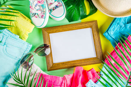 Summer sale shopping concept, Colorful background with various bright color childrens womens clothes, glasses, sneakers, hat. Copy space flat lay, for banners, top view
