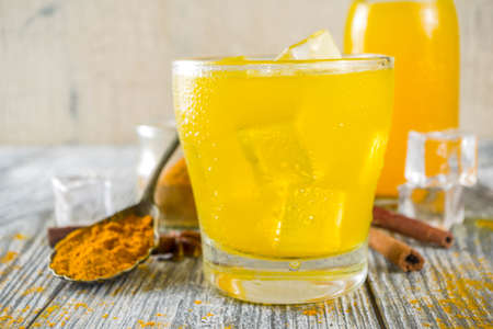 Iced Golden Cinnamon Turmeric Tea. Trendy cold drink with turmeric and spices, Wooden background copy space 免版税图像