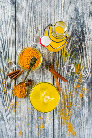 Iced Golden Cinnamon Turmeric Tea. Trendy cold drink with turmeric and spices, Wooden background copy space 写真素材