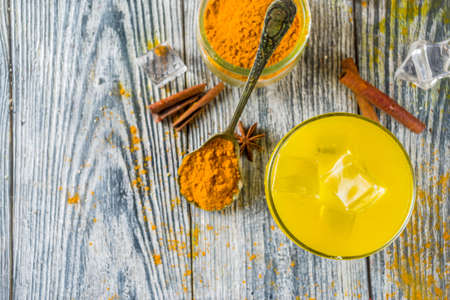 Iced Golden Cinnamon Turmeric Tea. Trendy cold drink with turmeric and spices, Wooden background copy space Фото со стока