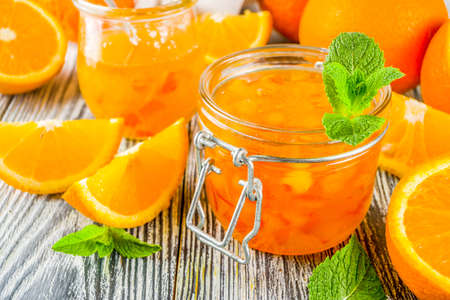 Homemade orange jam, with fresh sliced oranges and mint leaves, white wooden background copy space