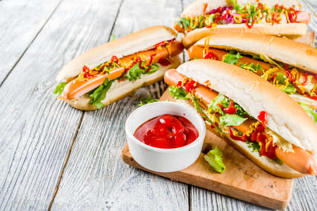Homemade hot dogs with fresh greens, sausages and sauces, white wooden background copy space top view