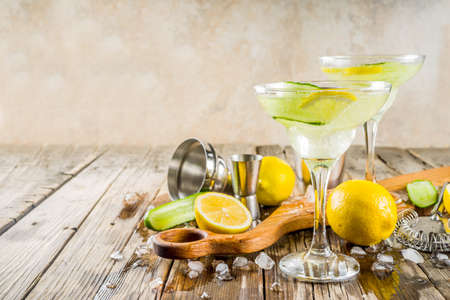 Trendy summer alcohol beverage, Low-Calorie and Low-Carb Tom Collins cocktail, with lemon and cucumber slices, old wooden background copy space