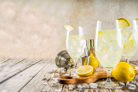 Trendy summer cold drink. St Germain French Spritz cocktail with lemon slices, old rustic wooden background copy space Stockfoto - 124188258