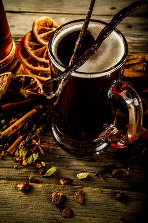 Bière chaude aux épices - vanille, cannelle, anis, agrumes. Boisson à la bière brune chaude. Espace de copie de fond en bois foncé